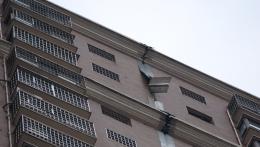 太危险!高层住宅楼外墙上3米长铁板被大风掀起
